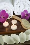 Brush and towels. Body brush on a bamboo tray with candles and towels Stock Image