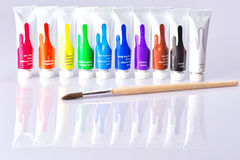 Brush tubes lies on the background with paints Royalty Free Stock Image