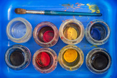 Brush and used watercolors in a blue box Royalty Free Stock Images