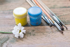 Brush on the wooden background with colored paints Royalty Free Stock Photos