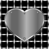 Brushed metal heart on a perforated background Stock Images
