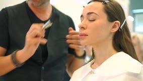 brusher 构成教训 化妆师和美丽的深色的女孩 股票录像