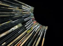 Brushes. Black background with many old brushes that form a semicircle Royalty Free Stock Photo