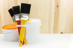 Brushes with can of paint against wooden background Royalty Free Stock Image
