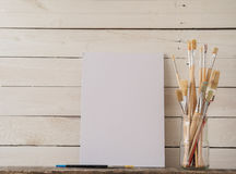 Brushes and canvas on wood. Paint brushes with a canvas on a white barn wood background Royalty Free Stock Photos