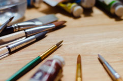 Brushes and Color Equipment On Wood Table. Brushes and color equipment on wood table in light Royalty Free Stock Photos