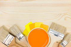 Brushes, color guide and paint can on wooden background Stock Photos