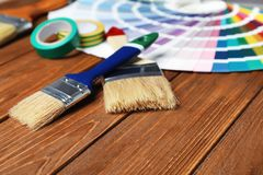 Brushes and color palette samples. On wooden background royalty free stock photo
