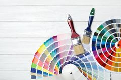 Brushes and color palette samples. On wooden background, flat lay stock images