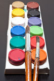 Brushes and colored paint artist on gray background Stock Image