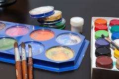 Brushes and colored paint artist on gray Stock Photography
