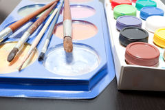 Brushes and colored paint artist on gray Stock Photos