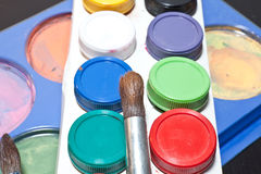 Brushes and colored paint artist on gray background Royalty Free Stock Photos