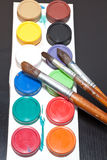 Brushes and colored paint artist on gray background Royalty Free Stock Photo
