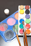 Brushes and colored paint artist on gray background Stock Photography