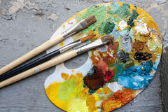 Brushes and colorful abstract oil colors paiters pallet, on grunge background Royalty Free Stock Photo
