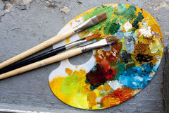 Brushes and colorful abstract oil colors paiters pallet, on grunge background Stock Photo