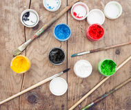 Brushes with colorful paints on old wood Stock Photos