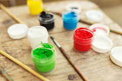 Brushes with colorful paints on old wood Royalty Free Stock Photo