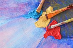 Brushes and colors on painted canvas Royalty Free Stock Photos