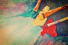 Brushes and colors on painted canvas Stock Images