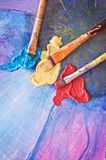 Brushes and colors on painted canvas Stock Image