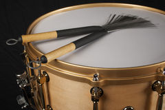 Brushes on a copper snare drum against a black background Stock Photo