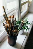 Brushes for drawing on a white window sill near the window. Brushes of different density and size for drawing on a white window sill near a window, next to a stock photography