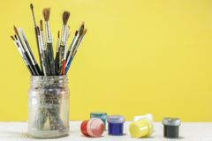 Brushes for drawing in a glass and jars with gouache on the table. Brushes for drawing in a glass, and a number of paint stock photos