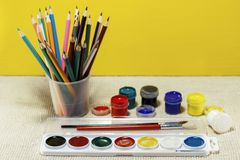 Brushes for drawing in a glass, and a number of paint. On rough fabric royalty free stock photography