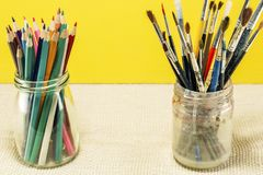 Brushes for drawing in a glass, and a number of paint. On rough fabric stock photo