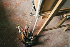 Brushes for drawing on an old wooden easel, stand on the floor. Brushes of different density and size for drawing on an old wooden easel, stand on the floor stock image