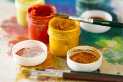 Brushes for drawing and several open jars of gouache royalty free stock photography