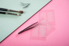 Brushes, fake lashes, tweezers and artificial eyelid crease double tapes for eye makeup on pastel rose pink and mint green stock images