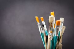 Brushes and grey wall. Paint brushes against dark grey background royalty free stock image