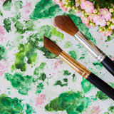 Brushes and hand made watercolor abstract floral background. Romantic concept of spring, lifestyle, hobbies. Top view Stock Photos