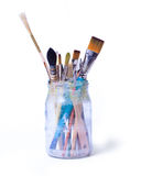 Brushes in a jar. Paint art brushes in a glass jar isolated over white background stock photo