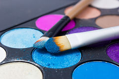 Brushes for make-up on the eye shadow palettes. Royalty Free Stock Photos
