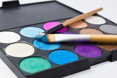 Brushes for make-up on the eye shadow palettes. Stock Photos