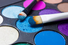 Brushes for make-up on the eye shadow palettes. Royalty Free Stock Images