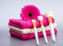 Brushes for make-up  on towel with  big pink flower Stock Photos