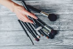 brushes for makeup in hands on wooden background stock photo