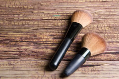 Brushes for makeup scattered chaotically on wooden background Royalty Free Stock Photo