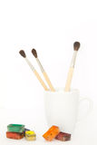 Brushes in a mug with paints. Brushes in a white mug with watercolor paints around royalty free stock photos