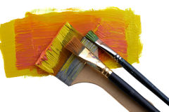 Brushes on a orange. Paint isolated on a white background stock images