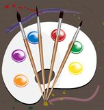 Brushes and paint. Four brushes and a palette with paint on the background of painted canvas Stock Images