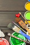 Brushes and paint on a wooden table. Painter tools. Workshop painter. Needs painting. Sales painting needs. Clutter on the workbench. Sales of color Stock Photography
