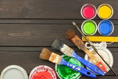 Brushes and paint on a wooden table. Painter tools. Workshop painter. Needs painting. Sales painting needs. Stock Photo