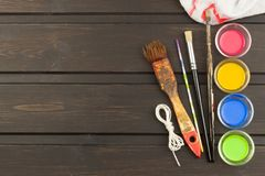 Brushes and paint on a wooden table. Painter tools. Workshop painter. Needs painting. Sales painting needs. Clutter on the workbench. Sales of color royalty free stock images
