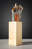 Brushes for painting in a wooden glass. It is a lot of brushes for painting in a wooden glass on a table on a dark background Stock Images